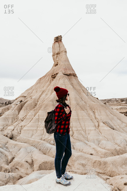Spain- Navarre- Female tourist standing in front of sandstone rock formation in Bardenas Reales