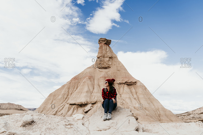 Spain- Navarre- Female tourist sitting in front of sandstone rock formation in Bardenas Reales