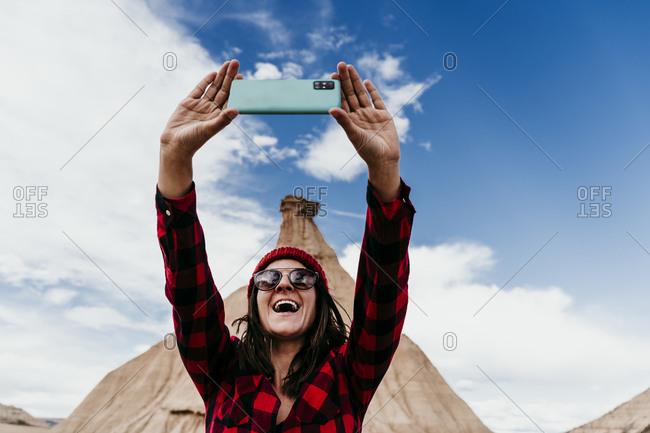 Spain- Navarre- Portrait of female tourist taking selfie in front of sandstone rock formation in Bardenas Reales