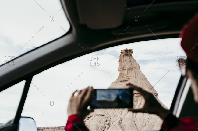 Spain- Navarre- Young woman sitting in car taking smart phone photos of sandstone rock formation in Bardenas Reales