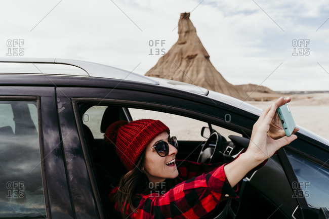 Spain- Navarre- Female tourist leaning out of car window taking smart phone photos of Bardenas Reales