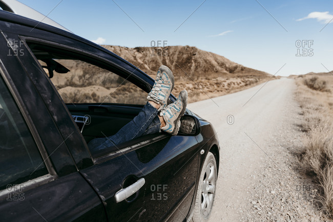 Spain- Navarre- Young woman sticking legs out of car window over  dirt road in Bardenas Reales