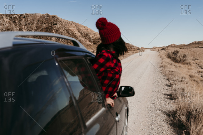 Spain- Navarre- Female tourist leaning out of car window over dirt road in Bardenas Reales