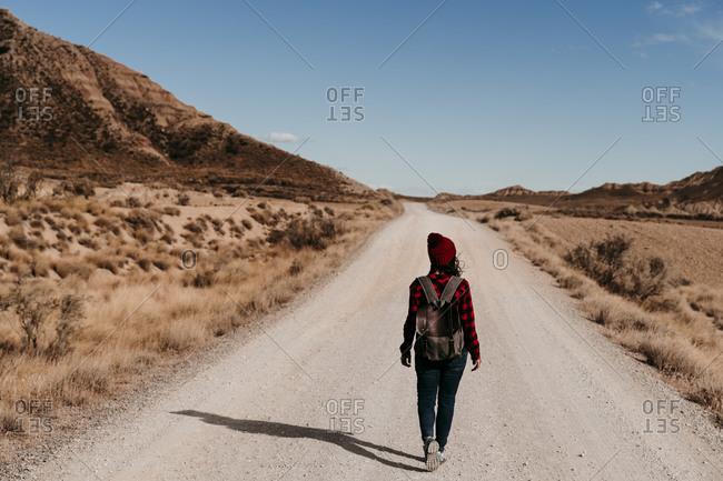 Spain- Navarre- Female tourist walking along empty dirt road in Bardenas Reales