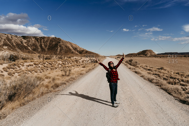 Spain- Navarre- Female tourist standing with raised arms in middle of empty dirt road in Bardenas Reales