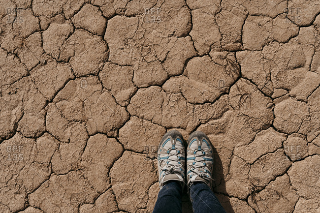 Spain- Navarre- Shoes of woman standing on dry cracked ground ofBardenasReales