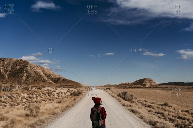 Spain- Navarre- Female tourist standing in middle of empty dirt road in Bardenas Reales