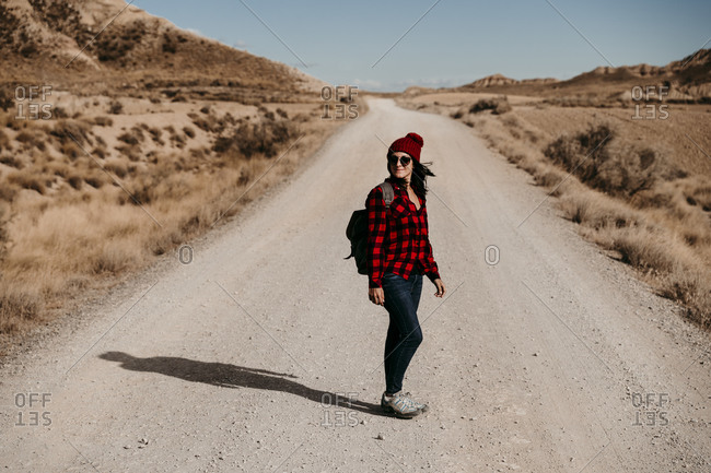 Spain- Navarre- Female tourist looking over shoulder in middle of empty dirt road in Bardenas Reales