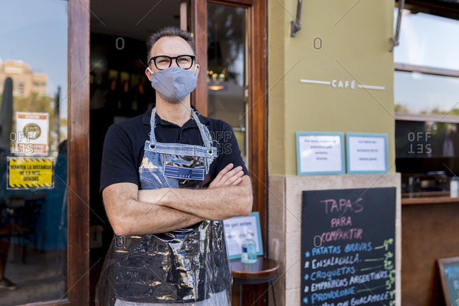 Male owner in face mask standing with arms crossed against cafe during COVID-19 crisis