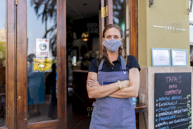 Confident female cafe owner wearing protective face mask during COVID-19 outbreak