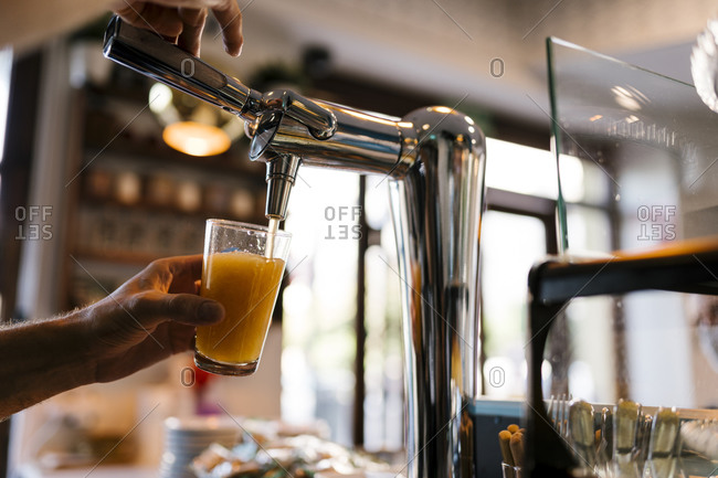 Bartender pouring beer in glass at cafe
