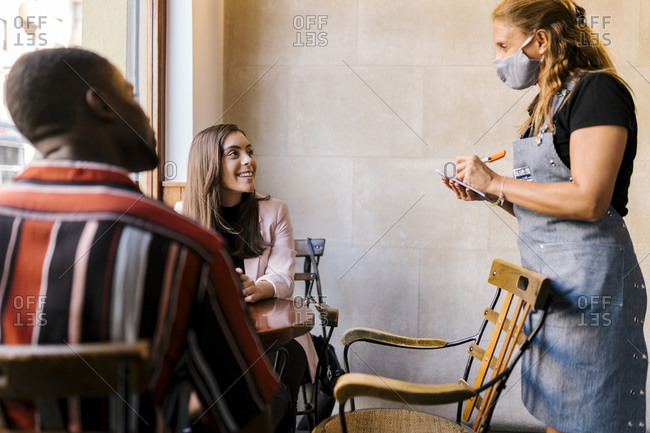 Waitress in protective face mask taking order from young couple at cafe