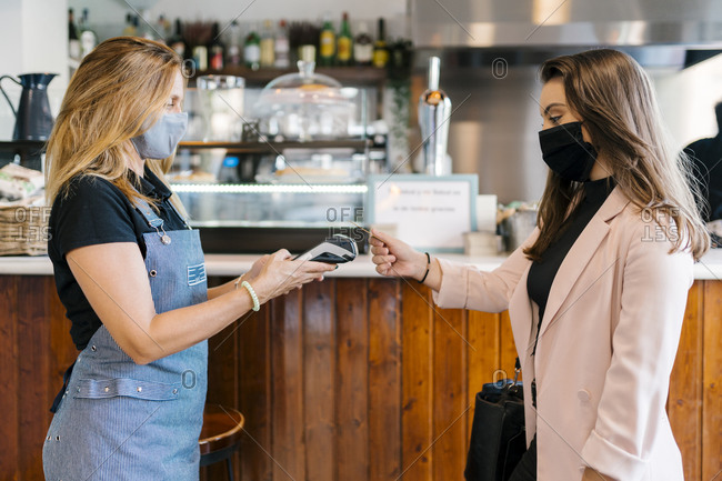 Businesswoman in face mask paying through credit card in cafe during coronavirus crisis
