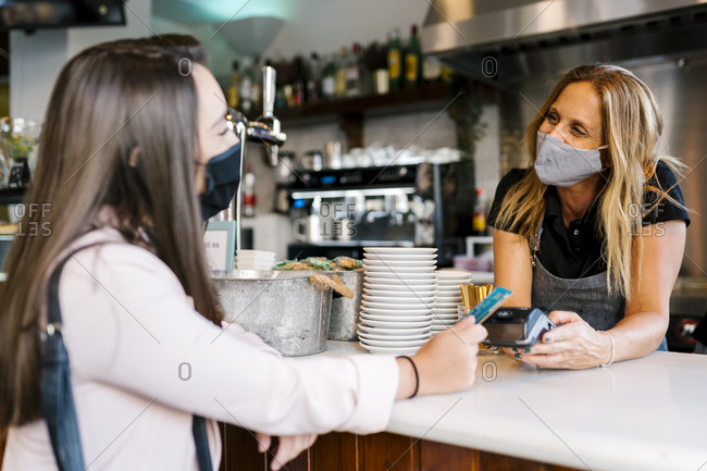 Businesswoman in face mask paying through credit card at counter in cafe during COVID-19 crisis