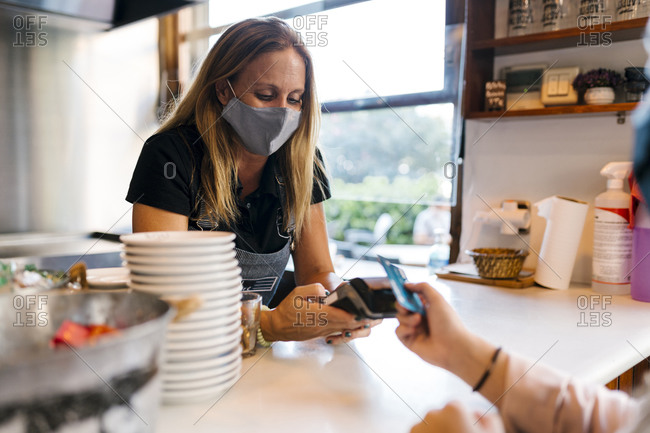Female cashier in face mask receiving payment through credit card in cafe during COVID-19