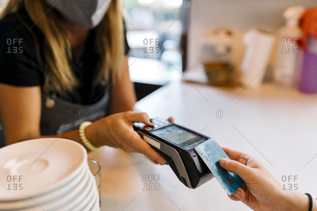 Female cashier receiving payment through credit card from customer in cafe during COVID-19