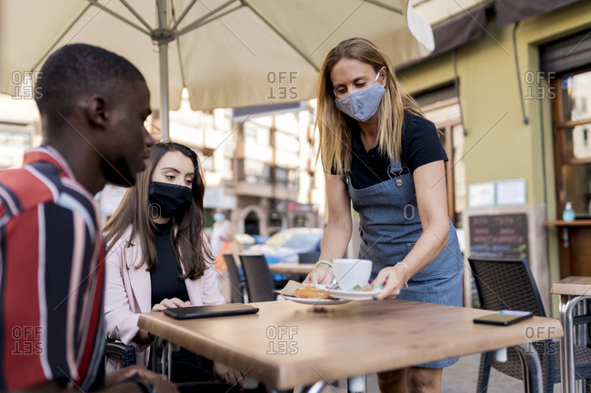 Waitress in face mask serving young couple at cafe during COVID-19 outbreak
