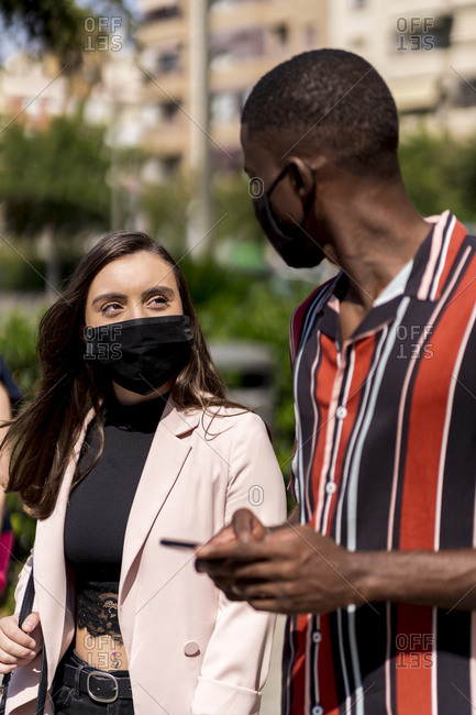Young couple wearing face masks while walking in city during COVID-19 outbreak