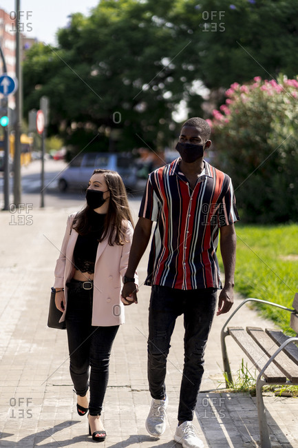 Young couple in face masks holding hands while walking in city during COVID-19 crisis