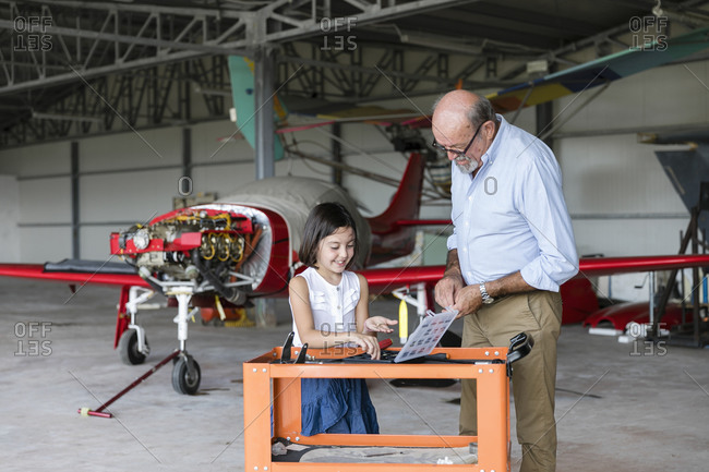 Granddaughter and grandfather selecting tools to fix aircraft