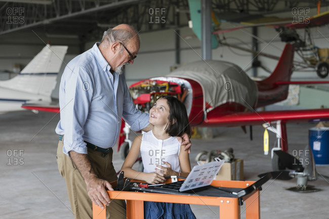 Grandfather and granddaughter looking at each other while standing in airplane hangar