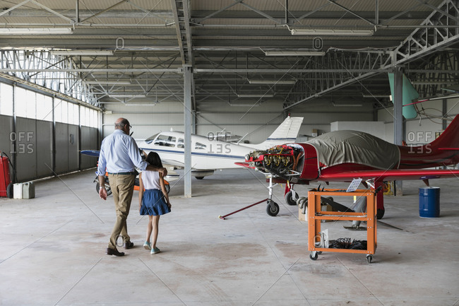 Granddaughter and grandfather walking in airplane hangar