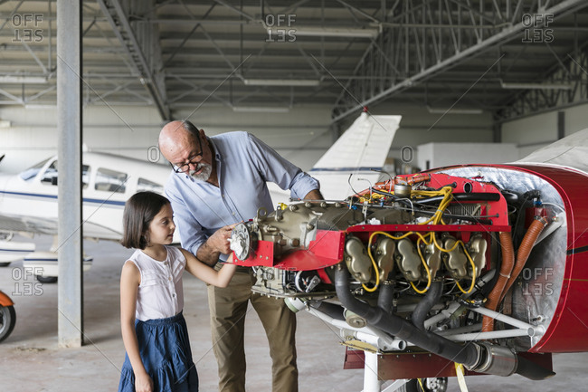 Grandfather showing how to fix airplane tool to granddaughter