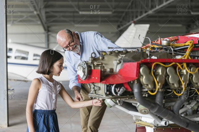 Grandfather showing how to fix airplane tool to granddaughter while standing in hangar