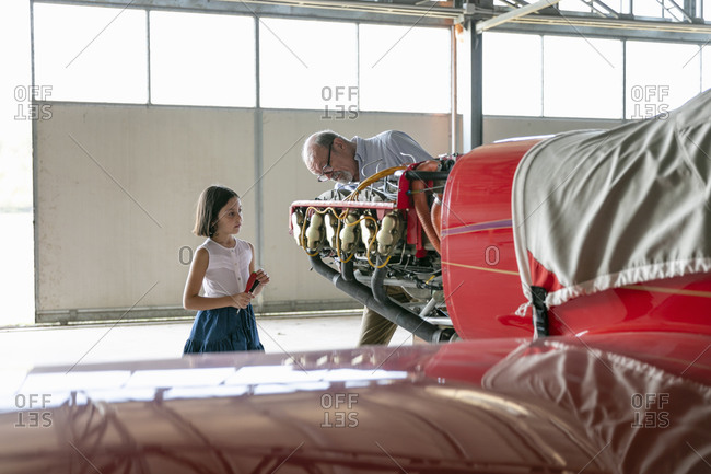 Grandfather concentrating while showing how to fix airplane tool to granddaughter while standing in hangar