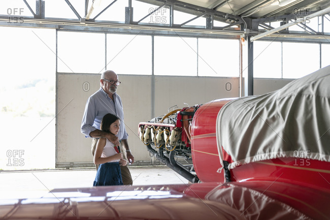 Grandfather and granddaughter looking at airplane while standing inside hangar