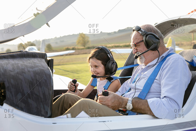 Granddaughter sitting with grandfather inside airplane at airfield