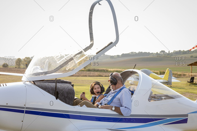 Little girl and grandfather getting ready to take off airplane at airfield