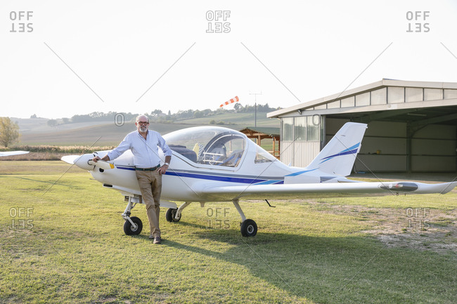 Senior man with hand on hip standing against airplane at airfield