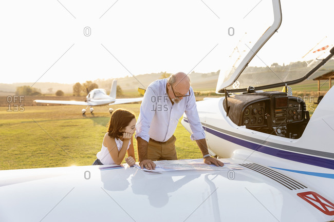 Grandfather and little girl looking at map on sunny day