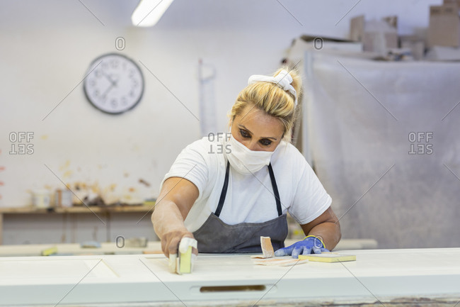Woman sanding wood while standing by workbench at workshop