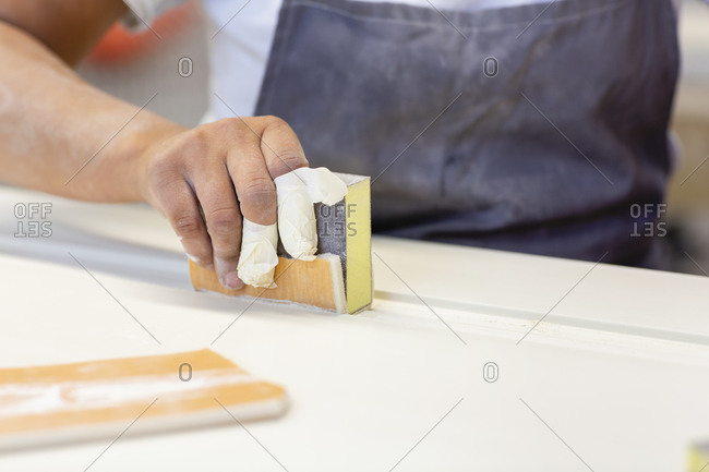 Carpenter hand sanding wood while standing at workshop