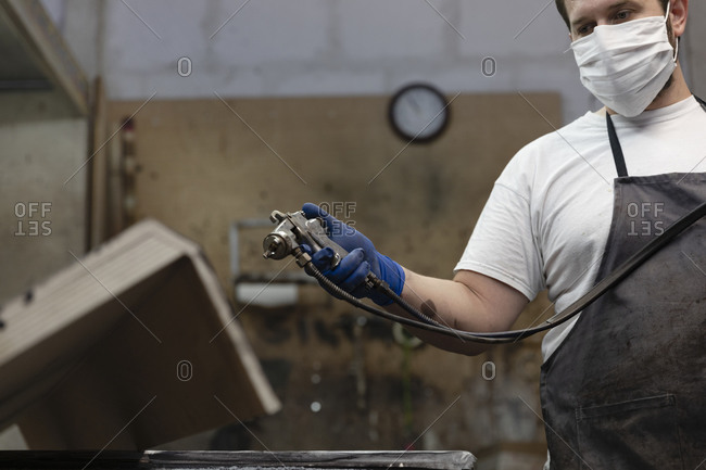 Man wearing face mask using spray paint gun on wood while standing at factory