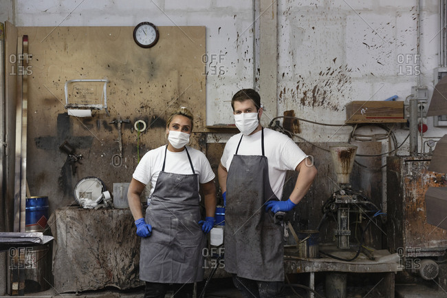 Confident carpenters standing with hand on hip at factory