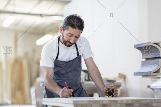 Man writing measurement on wood while standing at workshop