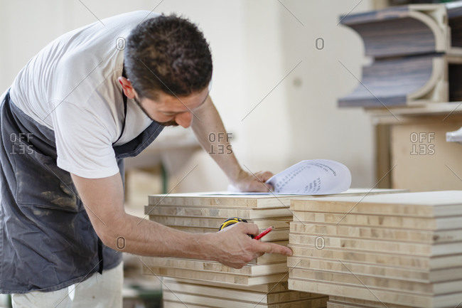 Man counting wood plank while working at workshop