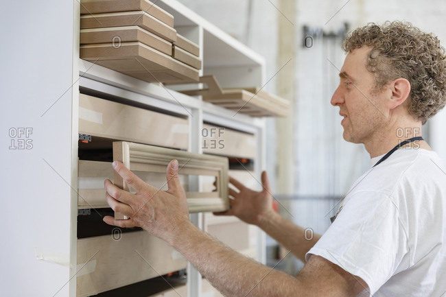 Mature man putting frames in drawer at workshop