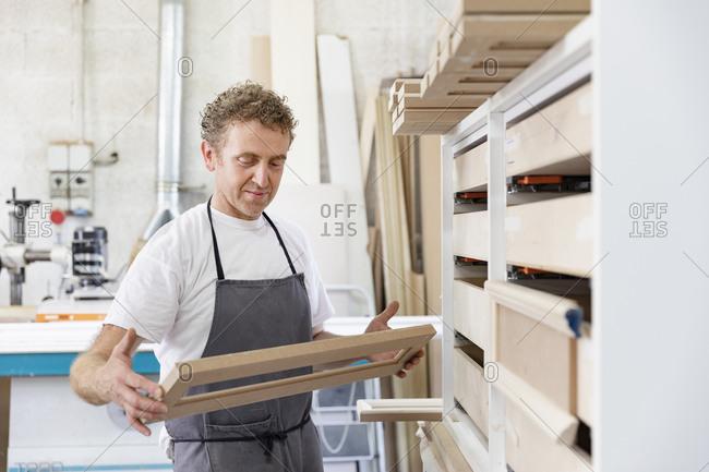 Carpenter holding frame while standing at workshop