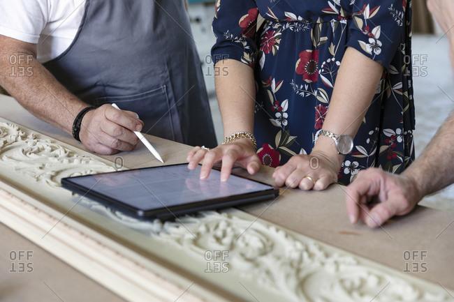 Carpenter and designer using digital tablet at workshop