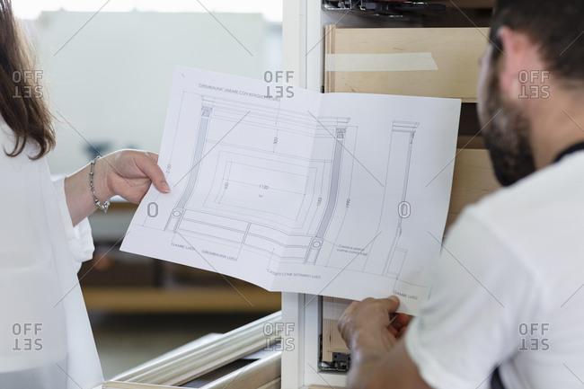 Interior designer showing design of drawer to carpenter while standing at workshop