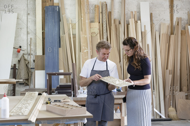 Female inspector and carpenter discussing inlay work while standing at workshop
