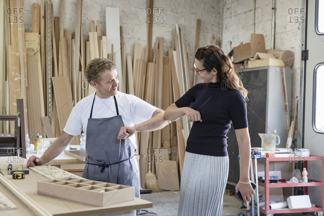 Smiling man and woman giving elbow bump while standing at workshop