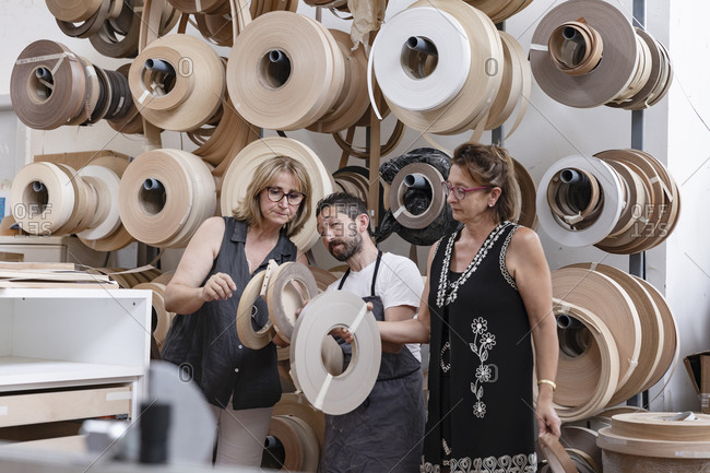 Interior designer and carpenter choosing spool while standing at workshop