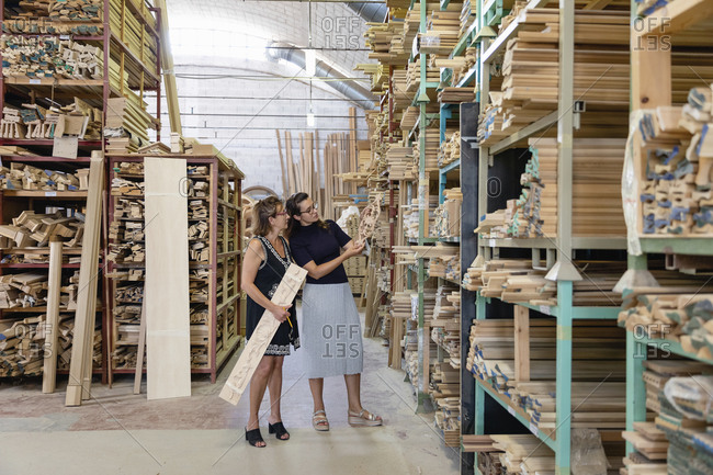 Women choosing ornate wood panel while standing in warehouse at factory