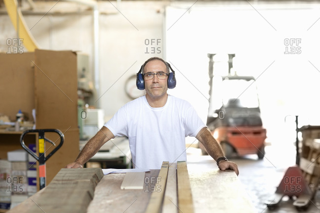 Man wearing earmuff while working at factory