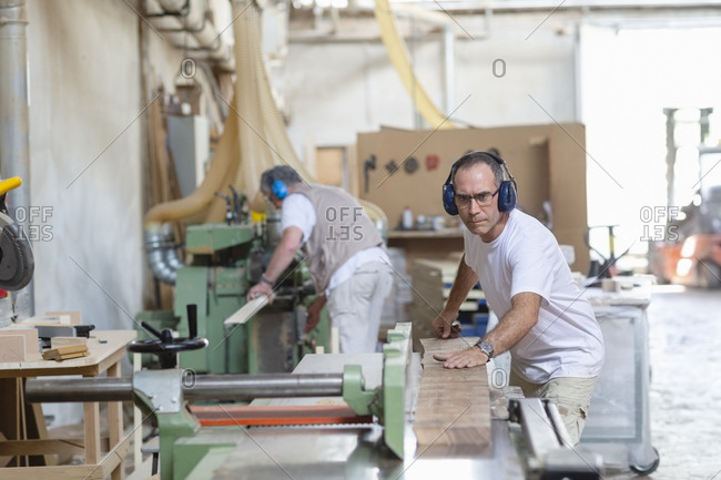 Coworkers wearing earmuff while sawing wood in machine at factory